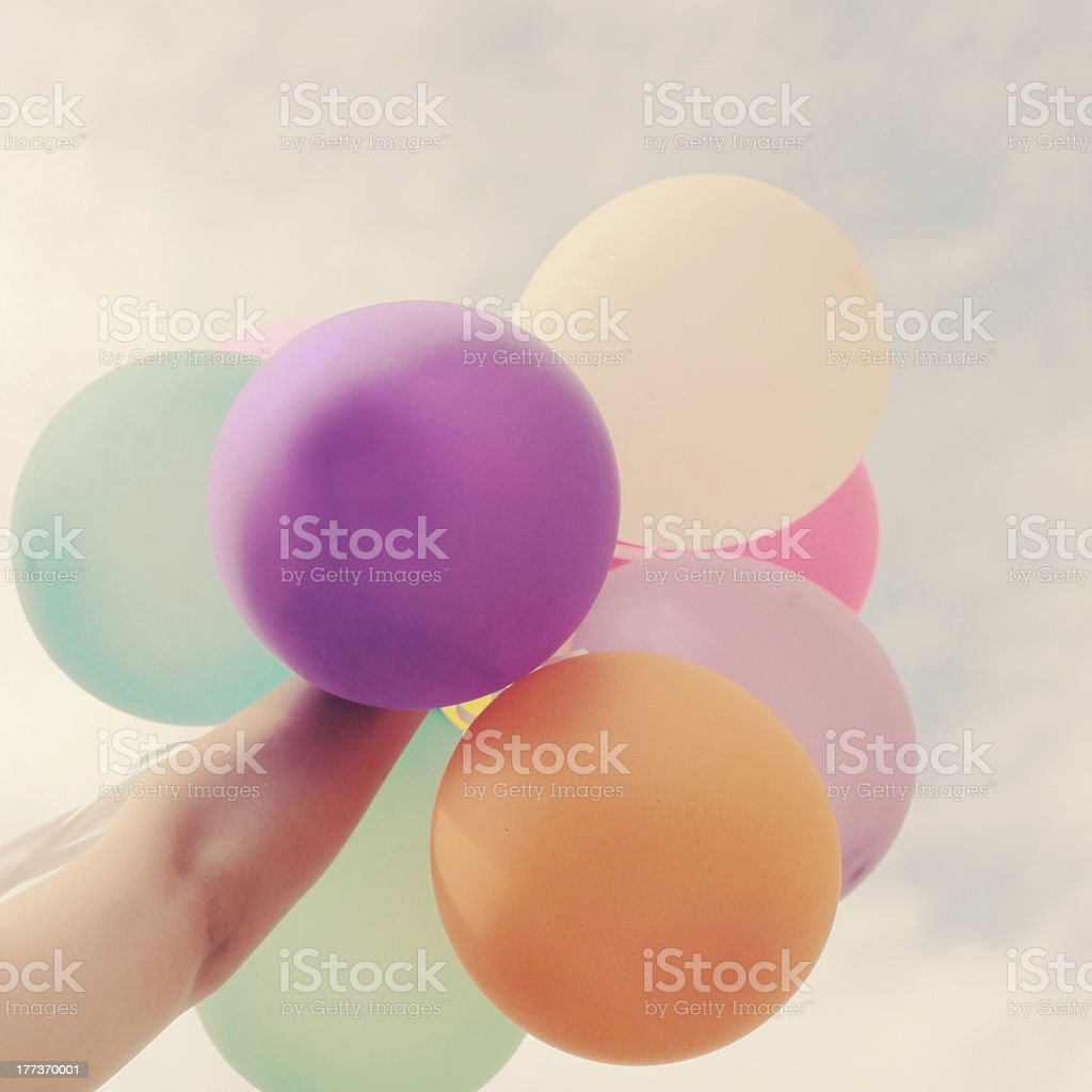Hand holding multicolored balloons with retro filter effect royalty-free stock photo