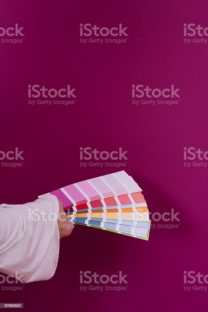 Hand holding multiple color charts against purple wall royalty-free stock photo