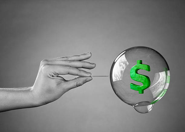 Hand holding needle about to pop bubble with dollar sign A hand about to burst a money bubble with a pin. Metaphor for an economic or financial bubble crisis. devaluation stock pictures, royalty-free photos & images