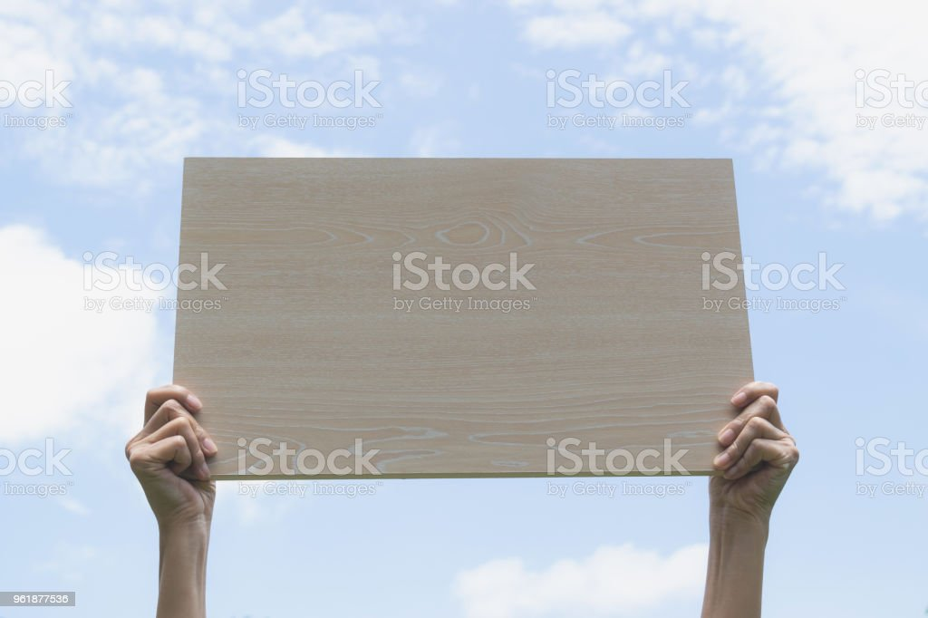 hand holding of wood this concept is for the text or advertising under the blue sky background. stock photo