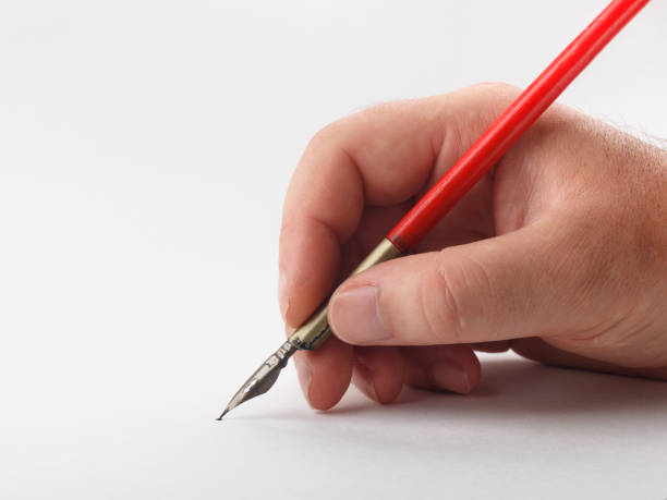 hand holding old inkpen on white paper background stock photo