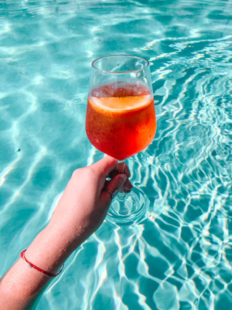 Hand holding Orange Aperol Summer Drink at the Swimming Pool stock photo