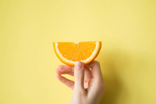 Hand holding orange on yellow background food concept stock photo