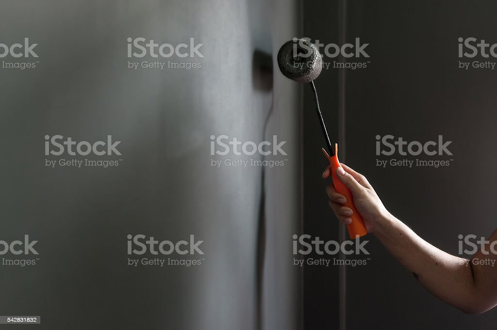 Hand holding paint roller applying grey paint on wall. stock photo