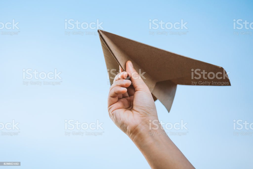 Hand holding paper airplane against the sky - foto stock