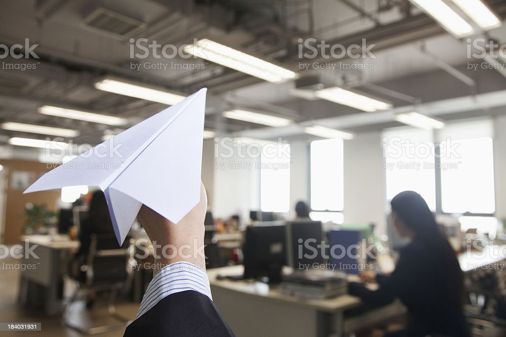 Hand holding paper airplane in office royalty-free stock photo