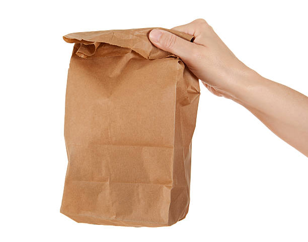 Hand Holding Paper Lunch Bag stock photo