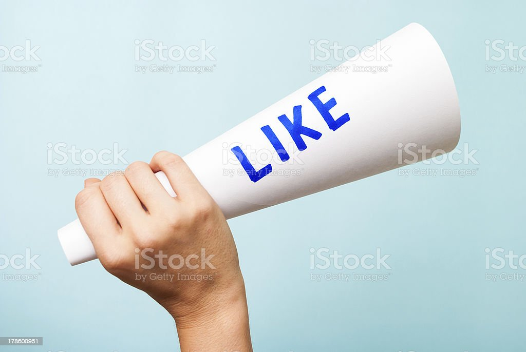 Hand holding paper megaphone with like word. Social media concept royalty-free stock photo