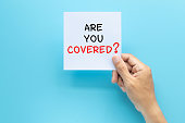 istock hand holding paper with question ARE YOU COVERED? isolated on blue background with copy space. travel insurance concept 1205218271