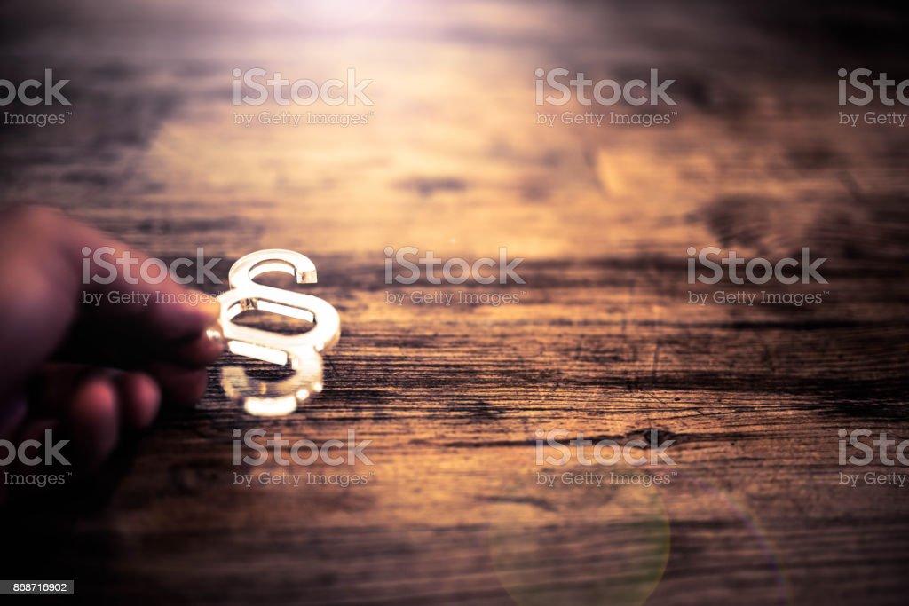 Hand hält Absatzsymbol über Schreibtisch aus Holz – Foto