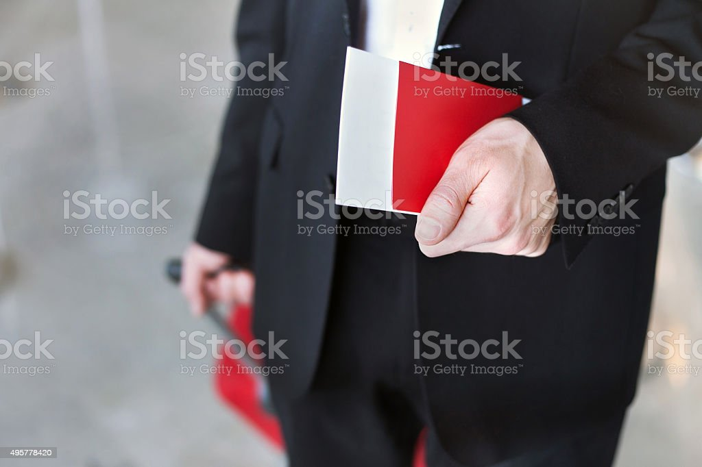 hand holding passport in airport stock photo