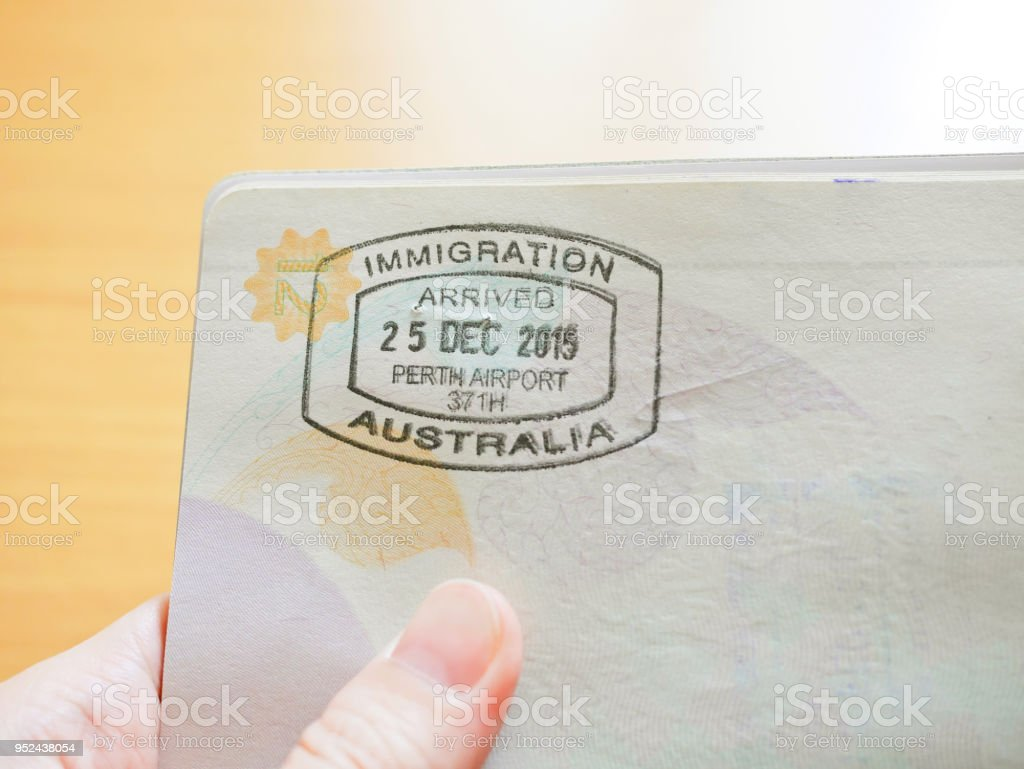 Hand holding passport with Australian immigration stamp stock photo