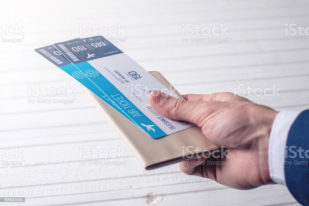 Hand holding passport with plane tickets on a white background. Concept of business travel stock photo
