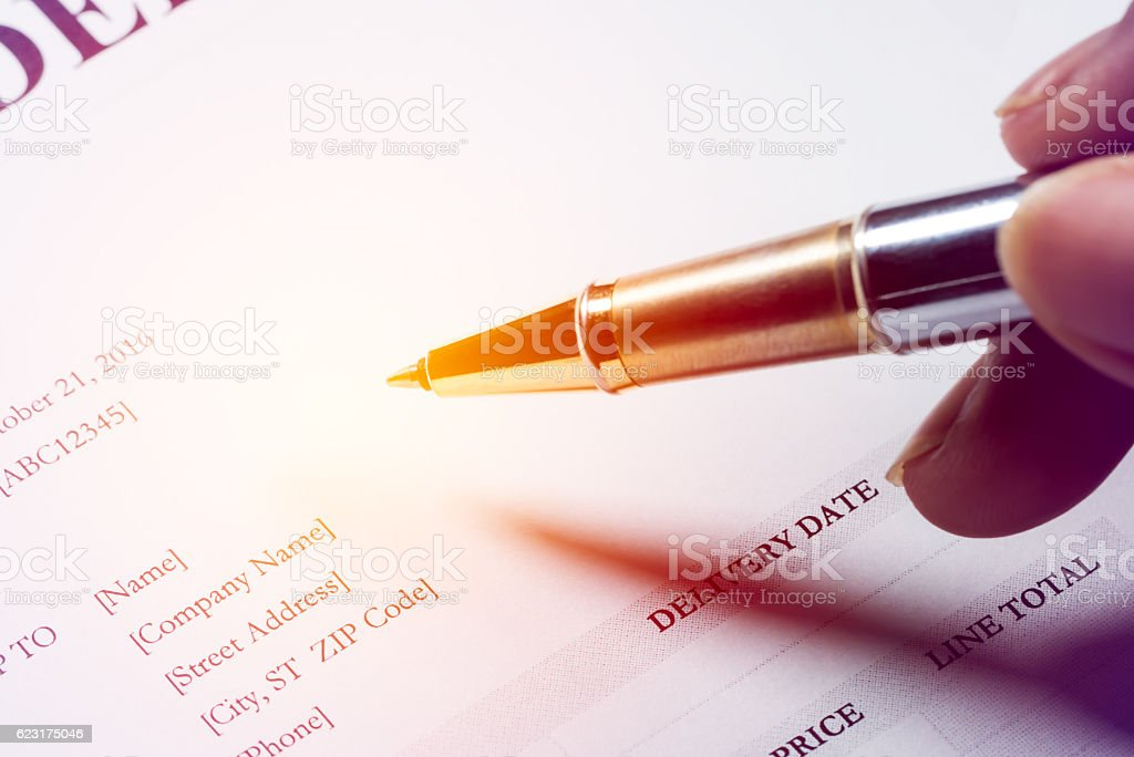 Hand holding pen to write text on purchase order for stock photo