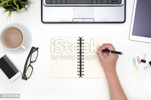 istock Hand holding pen with blank open notebook 637975286