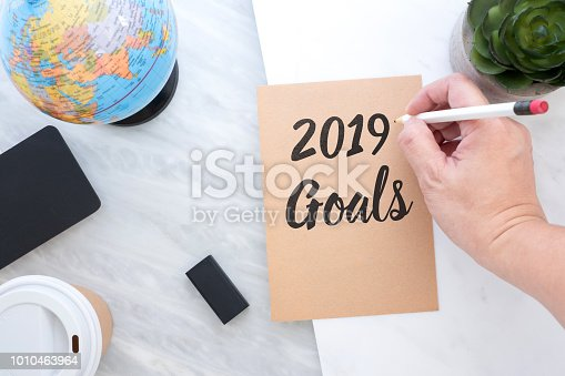 1034181368 istock photo Hand holding pen writing 2019 Goals on brown paper with blue globe,blackboard,coffee cup on marble table.new year's resolutions concept. 1010463964