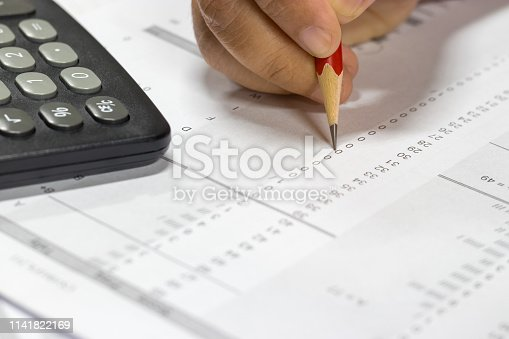 istock Hand holding pencil and calculator on paper of final grade for each course at the end of semester. The number of grade points a student earned in a given period of time. Grading in education concept. 1141822169