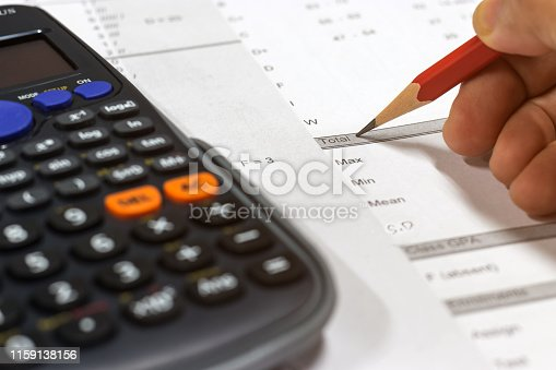 istock Hand holding pencil and calculator on paper of final grade for each course at the end of semester. The number of grade points a student earned in a given period of time. Grading in education concept. 1159138156