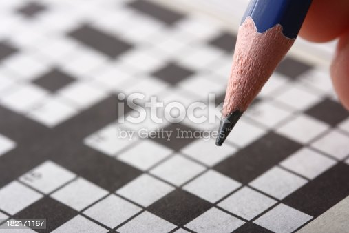 Close-up of a sharp pencil in front of a crossword.