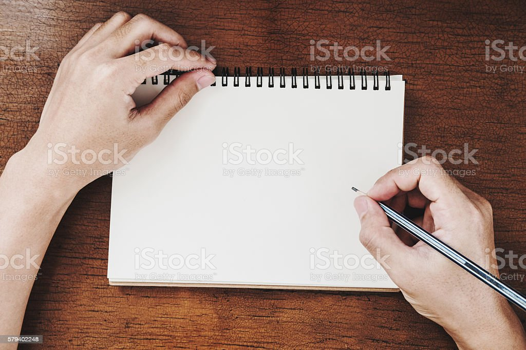 Hand holding pencil writing notebook on wooden desk, vintage tone stock photo