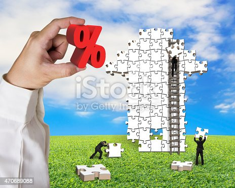 istock Hand holding percentage sign with business men building arrow pu 470689088