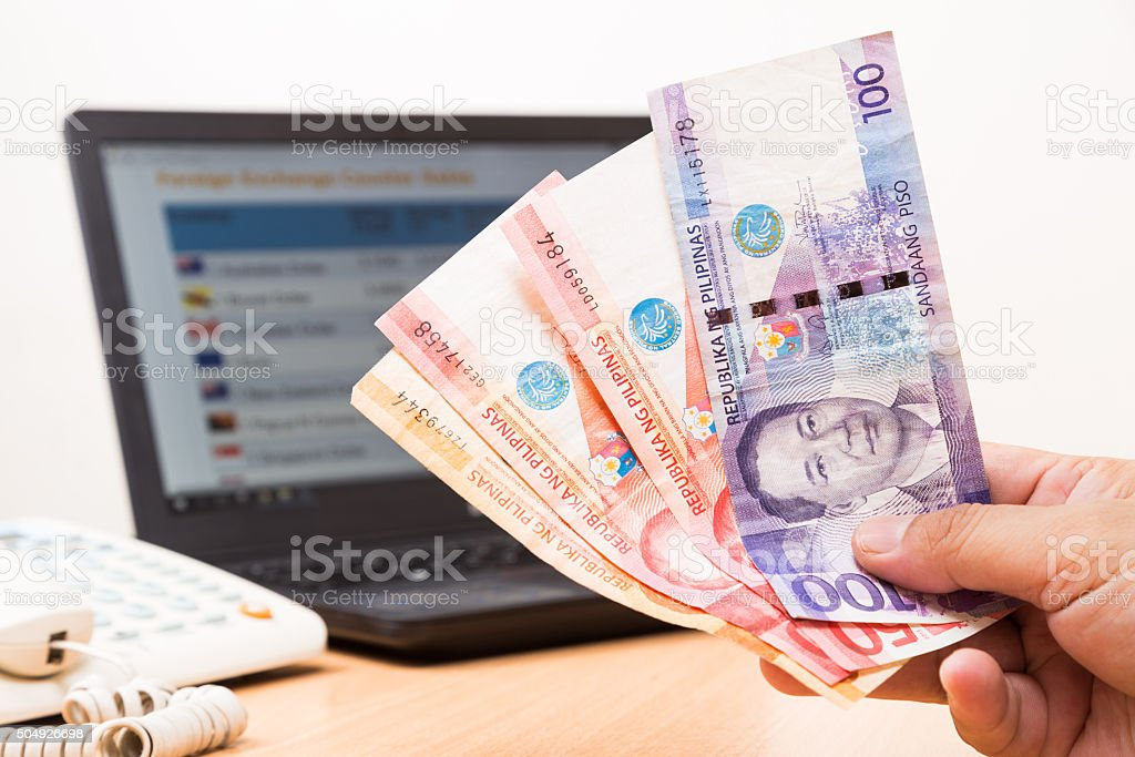 Hand holding Philippines Piso in office with computer in backgro stock photo