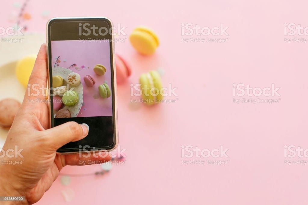 Hand hält Telefon und Aufnahme von leckeren bunten Macarons in Platte auf trendigen Pastell rosa Papier flach zu legen. Platz für Text. Modern Food-Fotografie-Konzept. Instagram Foto-workshop - Lizenzfrei Bunt - Farbton Stock-Foto