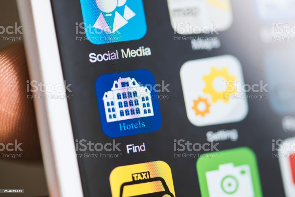 Hand holding phone, find hotels app on screen stock photo