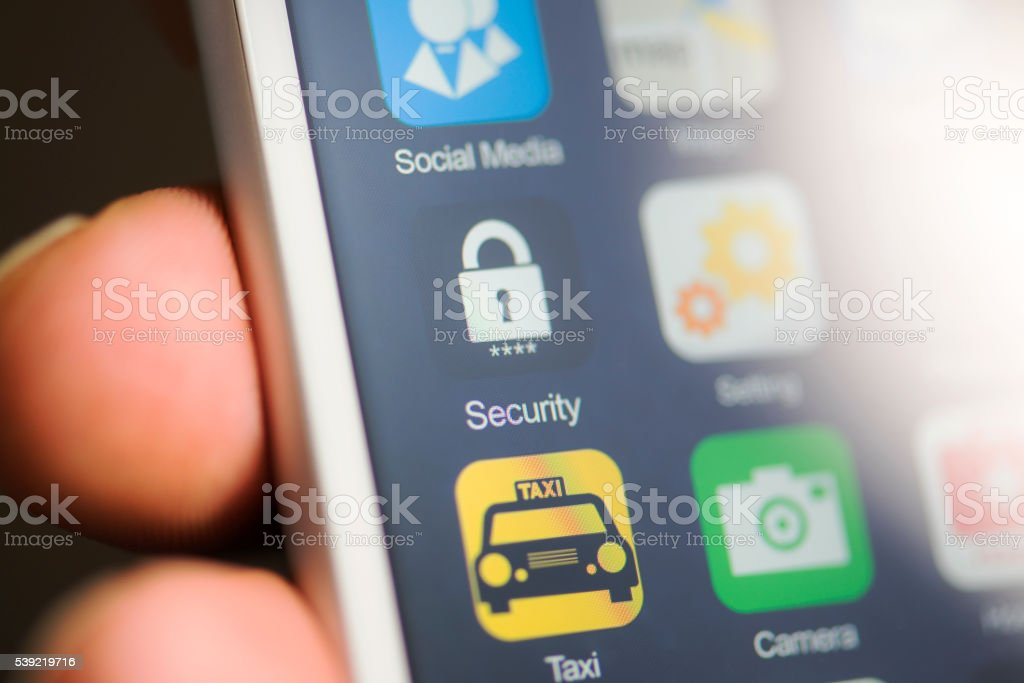 Hand holding phone, security app on screen Hand holding phone, security app on screen. Close-up Stock Photo