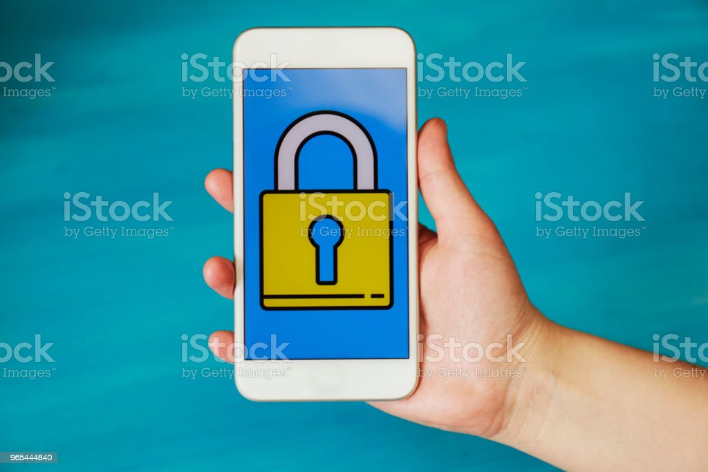 Hand holding phone, security icon on screen royalty-free stock photo