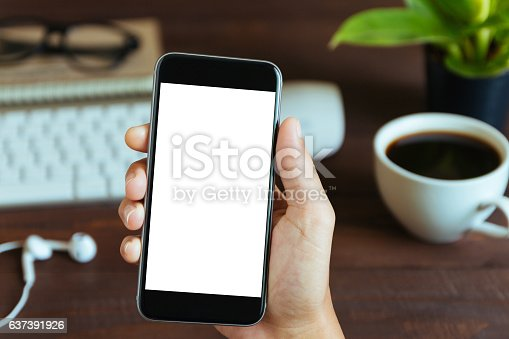 istock hand holding phone white screen over work table 637391926