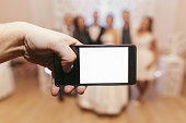 hand holding phone with empty screen and taking photo of happy wedding couple and guests at wedding reception.photo booth for bride and groom in restaurant.