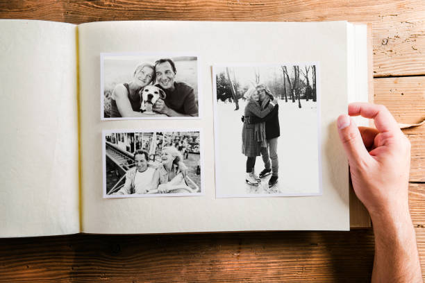 Hand holding photo album with pictures of senior couple. Studio Hand of unrecognizable person holding a photo album looking at various black and white pictures of senior couple. Studio shot on wooden background. album stock pictures, royalty-free photos & images