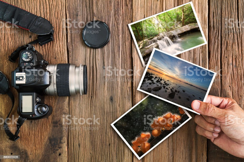 Hand Holding Photos With Old Camera Photos On Wooden