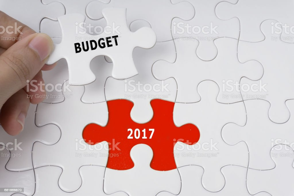 Hand holding piece of jigsaw puzzle with words Budget 2017. stock photo