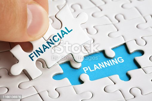 istock Hand holding piece of puzzle with words Financial Planning. 1166136976
