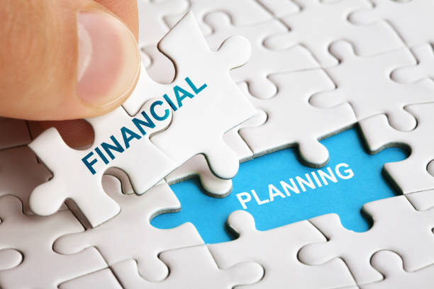 hand holding piece of puzzle with words financial planning. - financial planning stock pictures, royalty-free photos & images