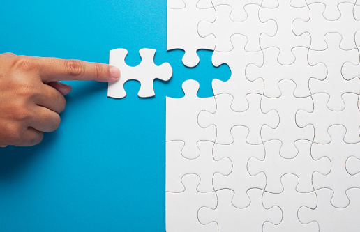 Hand holding piece of white puzzle on blue background.