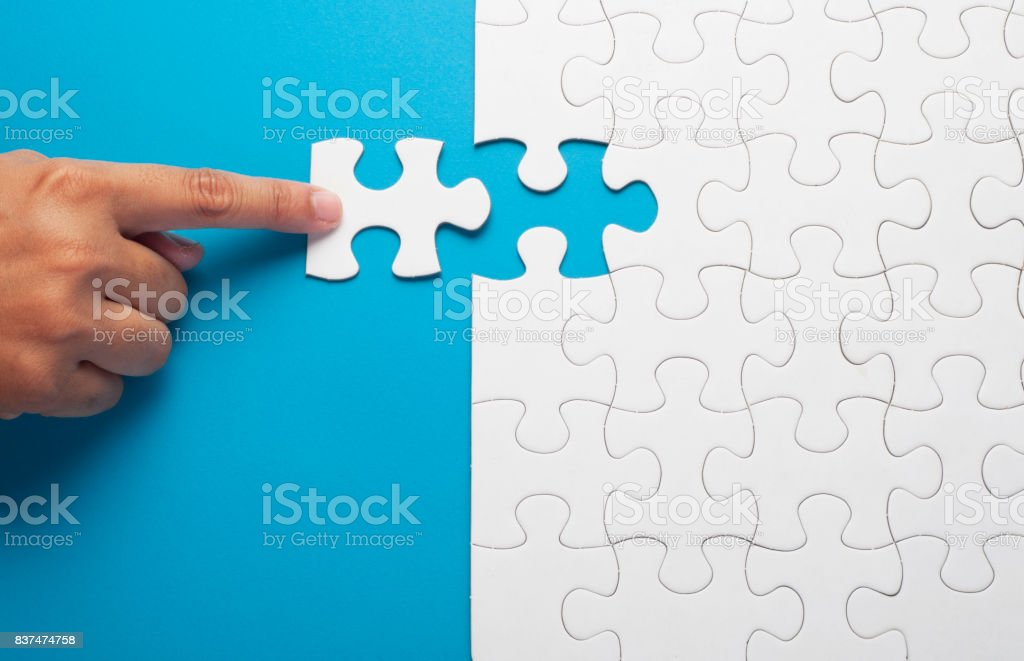 Hand holding piece of white puzzle on blue background. stock photo