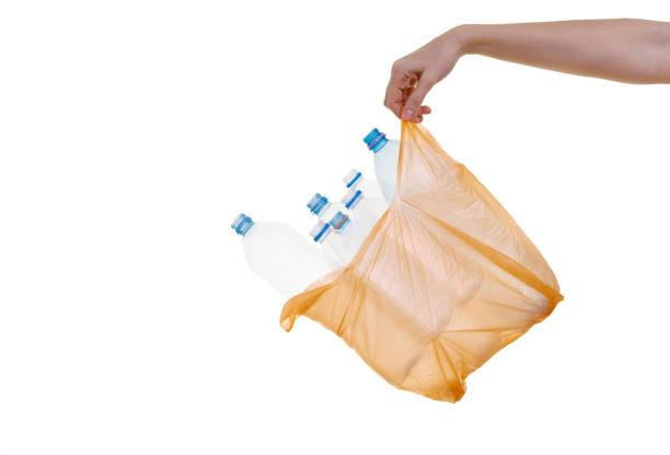 hand holding plastic bag with plastic bottles stock photo
