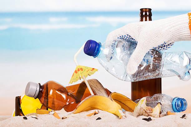Main tenant la bouteille en plastique sur la bande de déchets à fond de sable - Photo