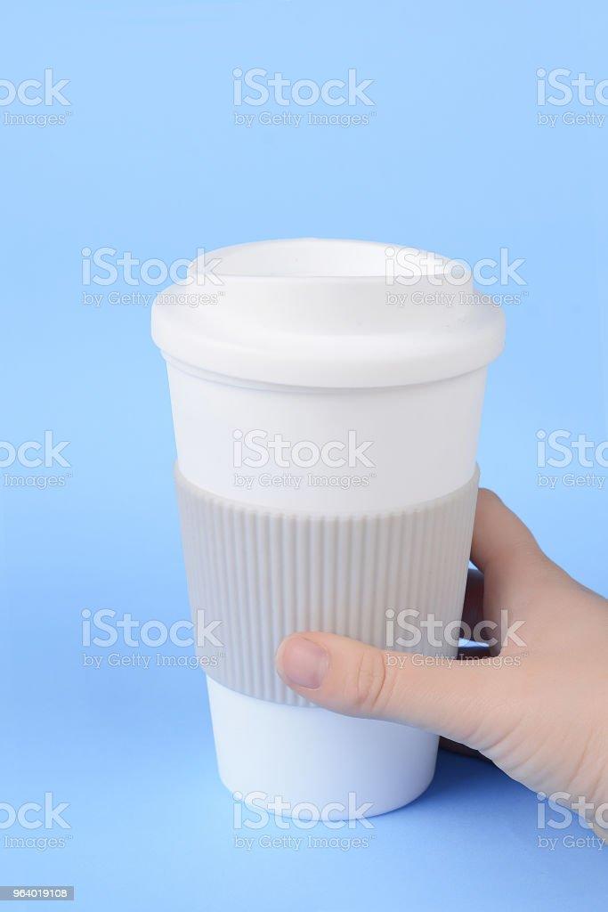 スリーブとプラスチック製のカップを持つ手。 - からっぽのロイヤリティフリーストックフォト