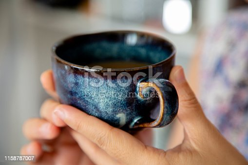 hand holding porcelain coffee cup