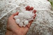 Hand holding quarter sized hail stones Denver Colorado