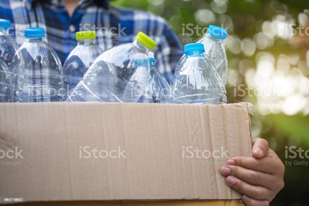 Hand holding recyclable plastic bottle in garbage bin. royalty-free stock photo