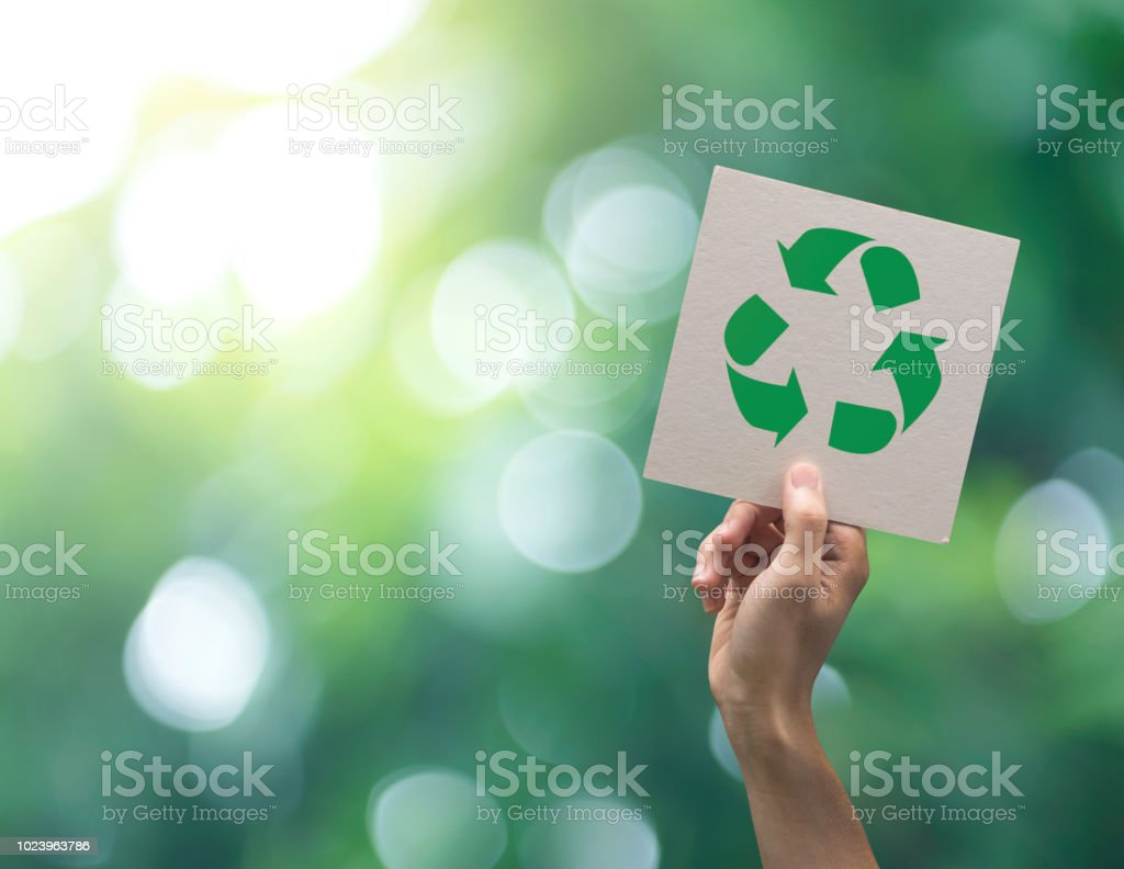 Hand holding recycle symbol on green bokeh background. eco and save the earth concept. royalty-free stock photo