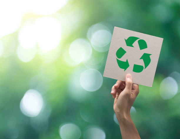 Hand holding recycle symbol on green bokeh background. eco and save the earth concept. stock photo