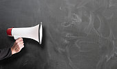 istock hand holding red and white megaphone against chalkboard 1149072755