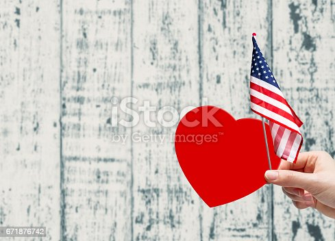 istock Hand holding red paper heart and USA flag 671876742