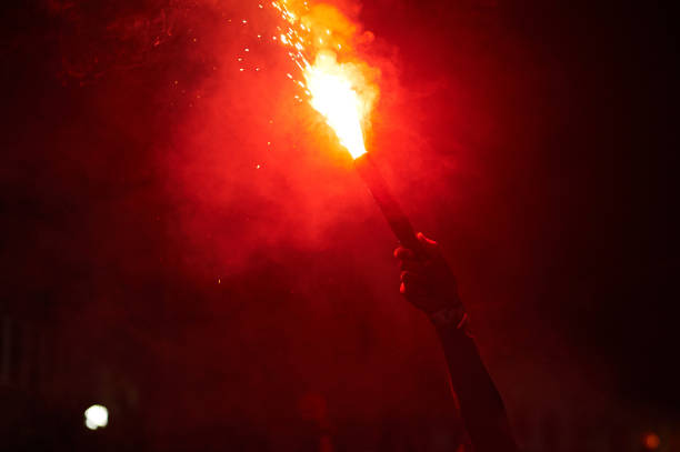 hand holding red torch hand holding bright red torch at night pyrotechnic effects stock pictures, royalty-free photos & images